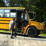 Very little boy, very big bus